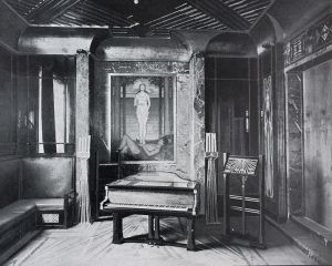 Peter Behrens - Interior de la casa en la colonis de Mathildenhöhe (Darmstadt), 1903- La imagen muestra una habitación que parece ser una sala de música, con un piano de cola corta en el medio y un atril de pie a su lado. El suelo y parte de las paredes están recubiertos de madera trabajada. Al fondo puede apreciarse un cuadro que representa a un hombre desnudo tumbado en el suelo y sobre él, como flotando, una mujer también desnuda (quizá una versión de la creación de Eva). El cuadro está rodeado por molduras de mármol negro jaspeado con vetas claras. A la izquierda de la imagen se puede ver parte de un sofá de respaldo alto y recto que parece estar situado bajo una ventana (no se vé la ventana, pero sí la luz que procede de ese lado). Pulse para ampliar.
