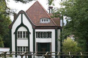 Peter Behrens - Casa en la colonia de Mathildenhöhe (Darmstadt), 1903 - La imagen muestra una vista exterior de una vivienda aislada de forma cúbica coronada por un tejado piramidal cubierto de tejas rojas. Los muros de la casa son blancos con los perfiles de las esquinas negros. Tiene dos pisos y una buhardilla, de la que se ve una ventana en medio del tejado rojo. Pulse para ampliar.