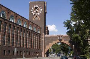 Peter Behrens: Sede central de los Laboratorios HOECHST en Frankfurt (1920-1925) - La imagen muestra un edificio de piedra rojiza, de aspecto como de fortaleza, coronado en el extremo más alejado por una torre en la que destaca un reloj de gran tamaño. Al lado de la torre parte un gran arco apuntado que parece conectar ese edificio con otro que no sale en el encuadre. Pulse para ampliar.