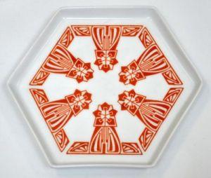 Peter Behrens - Fuente de porcelana (Deutscher Werkbund) - La imagen muestra una fuente de porcelana blanca de forma hexagonal que está decorada en tonos rojizos con un motivo vegetal muy estilizado y casi irreconocible que se reparte de modo simétrico por cada uno de los seis lados. Pulse para ampliar.