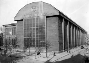 Peter Behrens: Fabrica de Turbinas de AEG en Berlín (1908). Fotografía de 1927. la imagen muestra una vista general del exterior del un edifico de forma prismática rectangular formado por dos cuerpos paralelos. El situado más a la derecha está en el borde de una calle y presenta un frente estrecho, recubierto con una cristalera y  coronado por un fronton poligonal que aloja el logotipo de la empresa. A su lado, hacia la izquierda, está la otra parte del edificio, también prismática y rectangular y de menos altura, que remata en u n tejado plano. Pulse para ampliar.