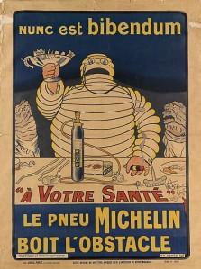 """Marius Rossillon (O´Galop): Cartel publicitario para los neumáticos Michelin (1898) - La imagen muestra un cartel en el que aparece una figura blanca formada por un montón de neumáticos blancos situados unos encima de otros. Está detrás de una mesa en la que en lugar de platos hay herramientas y una botella de aire comprimido para inflar neumáticos. La criatura alza en su mano derecha una copa llena a rebosar de fragmentos de vidrio y clavos y en la izquierda lleva un puro habano encendido. A su lado aparecen dos criaturas con aspecto fofo y desinflado que llevan un cartel que pone """"neumáticos"""". En la parte superior aparece la frase latina """"Nunc set bibendum"""" y en la parte inferior, """"A su salud: el neumático Michelin se bebe el obstáculo"""". Pulse para ampliar."""