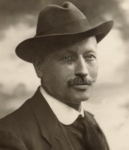 Marius Rossillon (O´Galop) en 1910 - La imagen muestra un retrato fotográfico del artista. Es un primer plano y aparece de tres cuartos, sin mirar directamente a la cámara, vestido con traje y corbata y luciendo sombrero. Tiene los ojos claros y lleva bigote. Pulse para ampliar.