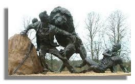 Ray Harryhausen - Escultura de David Livingstone en Blantyre, Lanarkshire (2004) - La imagen muestra una escultura en bronce de gran tamaño. En primer plano hay una roca y apoyado en ella un hombre vestido con ropas coloniales que se gira sorprendido en el momento de ser atacado por un gran león a sus espaldas. Pulse para ampliar.