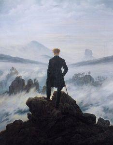 La imagen muestra un cuadro en formato vertical en el que podemos ver la figura de espaldas de un hombre en la cima de una montaña que contempla a sus pies un valle lleno de nubes, del que sólo asoman los picos de las montañas que hay enfrente. El hombre se apoya sobre un bastón y parece ensimismado mirando el panorama. Pulse para ampliar.