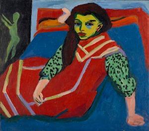 La imagen muestra el interior de una habitación en la que la mayor parte del espacio está ocupado por una cama cubierta por una colcha de color azul intenso. Sobre la cama está sentada y un poco recostada una chica joven que lleva un vestido rojo con mangas verdes. Su rostro está dibujado de un modo muy sumario, casi como si fuera un triángulo invertido, y el tono de su piel es verdoso. Pulse para ampliar.