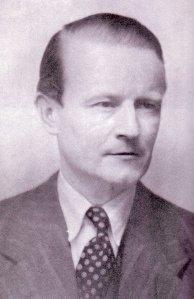 La imagen, una fotografía en blanco y negro, muestra un primer plano de un hombre, vestido con traje y corbata, que mira hacia la derecha y lleva el pelo de color claro peinado hacia atrás con gomina. Pulse para ampliar.