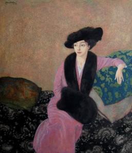 La imagen muestra a una mujer joven, sentada sobre un diván y que apoya su brazo izquierdo sobre un montón de cojines. Está vestida con un traje rosa y lleva sombrero, estola y manguitos de piel de color negro. Tiene la pìel muy blanca y sus ojos azules son grandes y tienen una expresión sosegada y risueña. Pulse para ampliar.