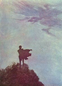 La imagen muestra un plano general de un hombre de espaldas al espectador que está en lo alto de una montaña observando el cielo. Sólo se aprecia su silueta y el viento parece agitar sus ropas mientras el cielo adquiere tonos malvas y rosados. Pulse para ampliar.