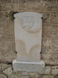 La imagen muestra la fotografía de una lápida de piedra que en la parte superior está decorada con un bajorrelieve que muestra a un unicornio alado sobre el que luce una estrella. Bajo él, la inscripción: