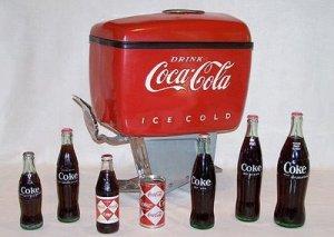 La imagen muestra un dispensador de Coca Cola que consta de una parte inferior de forma troncopiramidal invertida (la que va sobre la barra) de color metálico, coronada por una especie de depósito cuadrangular, de bordes redondeados, y de un llamativo color rojo sobre el que destaca las letras blancas con el nombre de la marca. Pulse para ampliar.