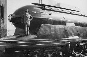 La imagen muestra una fotografía en la que aparece el frente de una locomotora. Sus formas se asemejan a las de un torpedo o un submarino porque tanto la parte superior, donde irían los maquinistas, como la inferior que sobresale para proteger la máquina y hacer de tope en las estaciones, están basadas en la línea curva y eso incluye el foco circular en el frontal, sobre las ventanillas de la cabina,. Loewy está subido a la protección inferior y mira a la cámara satisfecho. Pulse para ampliar.