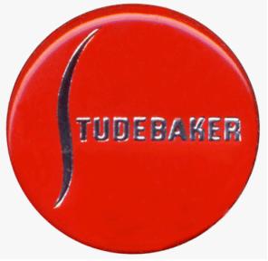 """La imagen muestra un logotipo o marca que consiste en un círculo de color rojo brillante sobre el que se destaca el nombre de la marca (Studebaker) en letras plateadas mayúsculas. La """"S"""" con la que empieza el nombre es una línea sinuosa que ocupa casi todo el alto del círculo. Pulse para ampliar."""