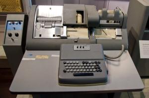 La imagen muestra una mesa sobre la que se dispone una máquina de gran tamaño que consta de dos grandes partes. Por un lado, la parte trasera,  formada por una pieza única con varios rehundidos en donde se sitúan los diferentes mecanismos. Y, unida por un grueso cable, la parte delantera que es una especie de teclado de mecanografía. Pulse para ampliar.