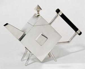 La imagen muestra una tetera con forma de rombo apoyado sobre uno de sus vértices por medio de cuatro patas cortas de sección cilíndrica. La parte superior de la tetera es una tapa triangular (que cierra la forma del rombo) coronada por una especie de punta de flecha. El pitorro es troncocónico y lel mango, un cilindro de ébano, se une al cuerpo romboidal a través de dos pieza cilíndricas. La parte central de la tetera presenta un hueco en forma de rombo también. Pulse para ampliar.