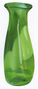 La imagen muestra un jarrón de vidrio verde muy fino que parece estar hecho de un material plástico ya que su forma, alargada, comienza siendo casi cilíndrica en la base, se vuelve un poco más bulbos y se estrecha en la parte superior como si alguien hubiese hecho presión con la mano y se hub hiera quedado la forma. Presenta una serie de hendidura a lo largo de su cuerpo como si los dedos del vidriero hubieran hecho las marcas, pero el aspecto general es de un objeto muy suave, sin aristas, como si estuviera modelado en barro. Pulse para ampliar.