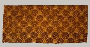 La imagen muestra un fragmento rectangular de tejido de fondo anaranjado sobre el que destaca un patrón decorativo formado por palmetas (estilizaciones geométricas de palmeras, de forma casi romboide) de color granate. El motivo de la palmeta se repite a intervalos iguales. Pulse para ampliar.
