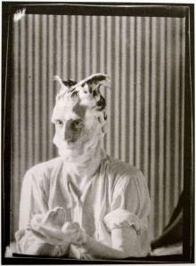 La imagen muestra una fotografía en blanco y negro donde se aprecia el plano medio de Duchamp vestido con una camisa blanca. Tiene casi toda la cara - salvo la nariz y los ojos- embadurnada con espuma de afeitar. También lleva el pelo lleno de espuma de afeitar y lo ha modelado de manera que dos mechones salen de cada uno de los lados de su cabeza. Eso le da aspecto de búho. Pulse para ampliar.