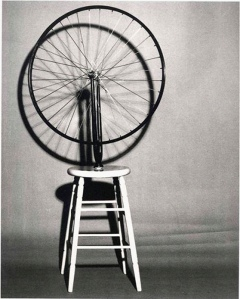 La imagen muestra una fotografía en la que aparece un taburete alto de cuatro patas sobre el que hay clavada una rueda de bicicleta. En realidad, la rueda, con sus radios, está sostenida por la pieza metálica que la une al cuadro de la bicicleta y esa pieza es la que está clavada en el taburete de modo que, si queremos, podemos hacer girar la rueda. Pulse para ampliar.