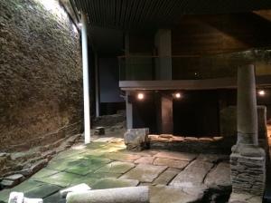 La imagen muestra el patio, cuyo suelo está cubierto con losas de piedra regulares. A la derecha de la imagen se aprecia el muro bajo y sobre él las columnas del pórtico. En la parte izquierda el patio está interrumpido por la muralla romana que se alza varios metros por encima del suelo. Pulse para ampliar.