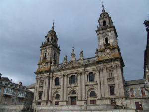 La imagen muestra la fachada de la catedral de Lugo. Consta de un cuerpo inferior de forma rectangular, con tres pisos de altura y decorado con columnas adosadas y un fronton triangular sobre la parte central. En ambos extremos se levantan dos torres con campanario de sección cuadrada. Pulse para ampliar.