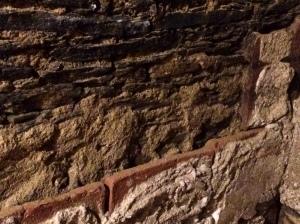 La imagen muestra la parte inferior de un muro de piedra. Se aprecia, en la base, como ese muro está recubierto con tejas rectangulares de cerámica puestas contra él de modo que dejan una cámara de aire por la que escurriría la humedad que se formara en ellos. Sobre estas tejas  puede verse parte del revestimiento del muro sobre el que iría la decoración de frescos pintados. Pulse para ampliar.