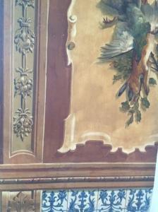 La imagen muestra un pequeño fragmento de muro en el que en la parte inferior se ve una decoración que imita azulejos decorados con elementos vegetales de color azul sobre fondo blanco. Sobre él, una pintura al fresco que representa una perdiz y una liebre muertos colgados junto con ramas de árbol. Pulse para ampliar.
