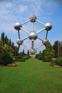 La imagen muestra una avenida ajardinada al final de la cual se eleva la estructura del  Atomium. Son siete esferas de acero y vidrio unidas por tubos demoro que reproducen el modelo tridimensional gigantesco de una molécula de hierro elemental. Pulse para ampliar.