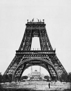 La imagen muestra la parte inferior de la Torre Eiffel, una obra de ingeniería construída en su totalidad en hierro, que se convirtió en el elemento más representativo de la ciudad de París desde entonces. En la fotografía se ven los cuatro pilares que soportan la torre y el segundo cuerpo, más estrecho, lo que le da un aspecto de pirámide truncada. Pulse para ampliar.