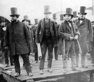 La imagen muestra una fotografía en la que en primer plano aparecen cuatro hombres, todos vestidos de manera similar con levitas abrochadas, frondosas patillas y tocados con sombreros de copa bastante alta. El primero por la izquierda es John Scott Russell, un hombre de gran envergadura, que mira hacia la izquierda. Un poco por detrás de él está otro hombre de pie que sostiene en su mano derecha lo que parecen ser unos planos enrollados. El tercer hombre, un poco más adelantado, es el ingeniero Isambard Kingdom Brunel que mira también hacia la izquierda mientras sostiene con sus manos una especie de tarjeta a la altura de su estómago. Está fumando un gran puro. Detrás de él aparece otro hombre con similar vestimenta que parece mirar a Brunel. Pulse para ampliar.