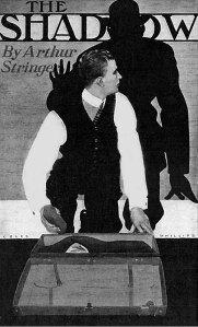 La imagen muestra la portada de un libro. El título (The Shadow) aparece en la parte superior. El resto del espacio está ocupado por la imagen de un hombre inclinado sobre una maleta abierta.  Está girado parcialmente hacia atrás. Y es que detrás de él vemos la sombra de otro hombre tocado con un sombrero que alza una mano amenazante sobre él. Pulse para ampliar.