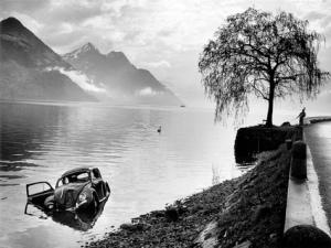 La imagen muestra una fotografía en banco y negro con un plano general en el que se aprecia a la izquierda un lago y a la derecha el arcén de una carretera. En medio y hacia el fondo, un árbol solitario que crece a la orilla del lago. A la izquierda y en primer plano, se aprecia un coche semihundido en el agua con una de sus puertas abiertas. Al fondo, bordeando el algo, puede apreciarle la silueta de las montañas. Pulse para ampliar.