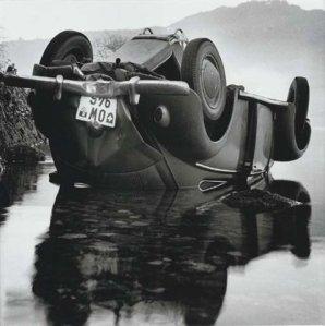 La imagen muestra un coche volcado con las ruedas hacia arriba en medio de un lago. El agua refleja el coche, de modo que se ve en su posición normal en el reflejo que se ve en el agua. Pulse para ampliar.