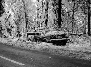 La imagen muestra en la parte central, un coche que se ha salido de la carretera y se ha estrellado contra los árboles del bosque que rodea la calzada. Parte de las ramas, completamente cubiertas de nieve, han caído sobre el techo del vehículo y lo han aplastado. Pulse para ampliar.