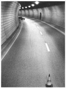 La imagen muestra el interior de un túnel visto desde un punto de vista elevado. La carretera traza una pequeña curva. En primer término hay un cono para indicar un peligro y al fondo, casi imperceptible, un coche que ha chocado contra una de las paredes del tunel. Pulse para ampliar.