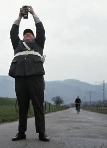 La imagen muestra a un gendarme en primer plano, visto desde abajo, que sostiene una cámara de fotos  por encima de su cabeza. Está sonriendo. Está situado en medio de una carretera estrecha y al fondo se aprecia cómo se acerca un hombre en motocicleta. Pulse para ampliar.