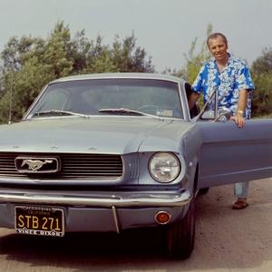 La imagen muestra a un hombre de pie al lado de un coche -es un Mustang- de color gris oscuro. Tiene la puerta del conductor abierta y él está tras ella, en actitud de entrar. Pero mira sonriendo a la cámara. Lleva sandalias, unos pantalones vaqueros y una camisa azul con flores blancas de estilo hawaiano. Pulse para ampliar.
