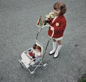 La imagen muestra a una niña pequeña, de unos cuatro años, vista desde arriba. Está de pie sobre una calzada y empuja un carrito de bebé de juguete donde lleva dos muñecas. La niña va vestida de blanco (zapatos, medias y vestido) y lleva puesta una chaqueta roja. Pulse para ampliar.