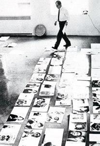 La imagen muestra una sala vista desde arriba. Sobre el suelo, desplegadas un montón de páginas dobles de revistas. Al fondo, de pie, paseándose entre ellas con un papel en la mano, Alexei Brodovitch.