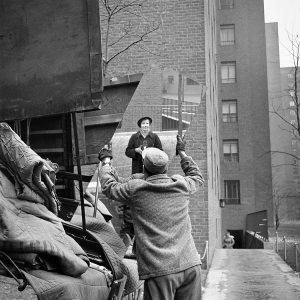 La imagen muestra la entrada de un edificio donde está aparcado un camión del que sólo se ve el portón trasero. Del camión un operario está bajando un espejo alargado en el que puede verse reflejada la imagen de Vivian, vestida con un abrigo oscuro y sombrero y con la cámara en la mano. Pulse para ampliar.