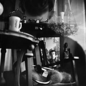 La imagen muestra el interior de un local que parece ser una tienda de antigüedades. Hay muchos objetos apilados: un taburete, una taza, una trompeta, una lámpara, un cuenco... Al fondo se ve un espejo y reflejada en ese espejo está Vivian con su cámara. Pulse para ampliar.