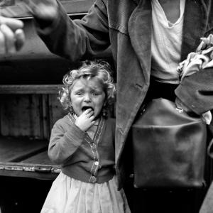La imagen muestra a una niña pequeña que se agarra a la chaqueta de un hombre del que sólo vemos su tronco y un brazo. La niña llora desconsoladamente mientras se lleva la mano a la boca. El hombre gesticula con su mano en lo que parece se una conversación con otra persona fuera de campo. Lleva una especie de maleta en la otra mano. Tanto él como la niña van vestidos de manera muy pobre. Pulse para ampliar.