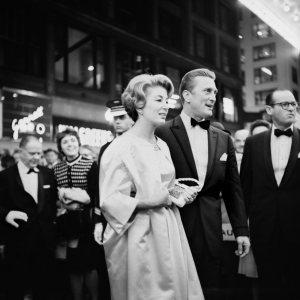 La imagen muestra al actor Kirk Douglas y a su mujer vestidos de gala, cruzando una calle. La imagen está tomada desde muy cerca, como si Vivian estuviera en medio del gentío que esperaba a los actores, que pasan delante de ella sin mirar. Pulse para ampliar.