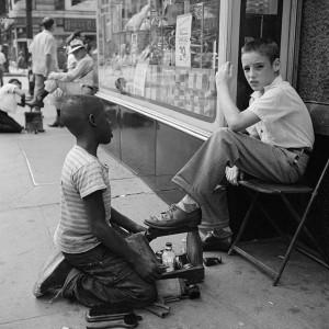 La imagen muestra la entrada de una tienda. En una silla plegable y mirando a la cámara, está sentado un chico de unos 11 años. Ante él, arrodillado, está un niño negro, de aproximadamente la misma edad que el otro que se dispone a limpiarle los zapatos. Al fondo puede verse a un hombre sentado en otra silla plegable con otro limpiabotas trabajando para él. Pulse para ampliar.