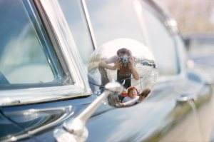 La imagen muestra la parte trasera de un espejo retrovisor de un coche. Es metálico y está reluciente. En la superficie cóncava del espejo se puede ver, en tamaño muy pequeño, a Vivian Maier enfocando con su cámara y delante de ella un carrito de bebé con dos niños pequeños que sonríen. Pulse para ampliar.