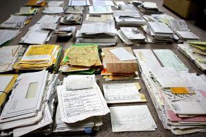 La imagen muestra una gran mesa, vista desde arriba, totalmente cubierta con pilas de papeles. Algunos son sobres de correspondencia comercial, otros son de correspondencia privada, hay muchos recortes de periódicos y revistas y también cuadernos de notas. Pulse para ampliar.
