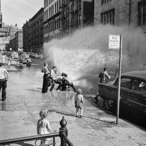 La imagen muestra una calle a pleno sol. En el medio del encuadre unos niños están forzando una boca de riego para refrescarse con el agua que sale de ella bajo la atenta mirada de otros chicos en la calle. Pulse para ampliar.