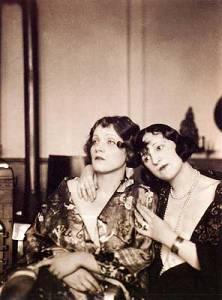 La imagen muestra una fotografía en blanco y negro donde aparecen sentadas, en plano medio, dos mujeres jóvenes. A la izquierda, Marlene Dietrich mira hacia la izquierda con semblante serio y las manos cruzadas sobre el regazo. A su lado, Ressel Orla le pasa la mano sobre el hombro y deja caer su cabeza hacia su compañera con un gesto un tanto pensativo. Pulse para ampliar.