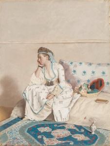 La imagen muestra a una mujer joven, sentada sobre unos cojines dispuestos en el suelo y cubiertos con telas. ante ella, una alfombra de vivos colores rosas y azules. Tiene el brazo derecho apoyado sobre la rodilla y mira hacia la izquierda con un ligero gesto de aburrimiento, aunque también con lo que parece una sonrisa reprimida. Pulse para ampliar.