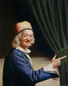 La imagen muestra un retrato en plano medio del pintor. Viste una camisola azul y un bonete rojo. Detrás de él aparece una cortina verde recogida y señala hacia la derecha con su índice. Mira directamente al espectador con una sonrisa amplia y cómplice que deforma su rostro en una mueca simpática. Pulse para ampliar.